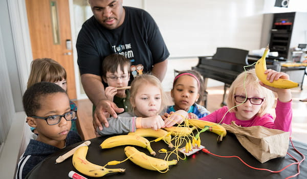 Jason Williams and camp participants playing the banana piano